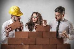 Zakenlieden en vrouw die een muur bouwen stock afbeeldingen
