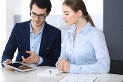 Zakenlieden en vrouw die tabletcomputer in modern bureau met behulp van Collega's of bedrijfmanagers op het werk partners stock afbeeldingen