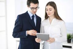 Zakenlieden en vrouw die tabletcomputer in modern bureau met behulp van Collega's of bedrijfmanagers op het werk partners stock afbeelding