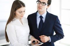 Zakenlieden en vrouw die tabletcomputer in modern bureau met behulp van Collega's of bedrijfmanagers op het werk partners stock foto