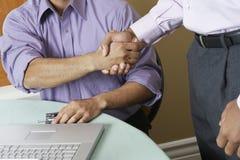 Zakenlieden het schudden dient bureau in royalty-vrije stock afbeelding