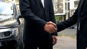 Zakenlieden het schudden dient overeenkomst in, die het informele lobbyen in openlucht samenkomen stock afbeelding