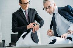 zakenlieden in kostuums en oogglazen die vergadering hebben royalty-vrije stock fotografie