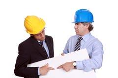 Zakenlieden met bouwvakkers en leeg karton stock foto's