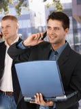 Zakenlieden op mobiele telefoon buiten bureau Stock Foto