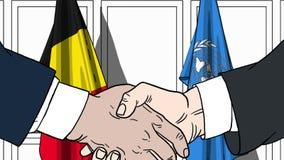 Zakenlieden of politicischokhanden tegen vlaggen van België en de Verenigde Naties Officiële vergadering of samenwerking royalty-vrije illustratie