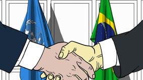 Zakenlieden of politicischokhanden tegen vlaggen van de Verenigde Naties en Brazilië Officiële vergadering of samenwerking stock illustratie