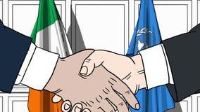 Zakenlieden of politicischokhanden tegen vlaggen van Ierland en de Verenigde Naties Offici?le vergadering of samenwerking royalty-vrije illustratie