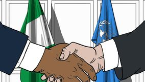 Zakenlieden of politicischokhanden tegen vlaggen van Nigeria en de Verenigde Naties Officiële vergadering of samenwerking royalty-vrije illustratie