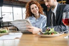 Zakenlui die bedrijfslunch hebben bij restaurantzitting die salade het drinken de krant eten die van de wijnlezing voorraad contr stock foto