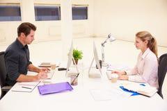 Zakenlui die bij Bureaus in Modern Bureau werken stock afbeeldingen