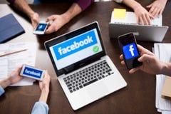 Zakenlui die digitale apparaten met de pictogrammen van het facebookembleem op de schermen met behulp van Royalty-vrije Stock Foto's