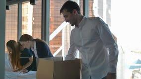 Zakenlui die dozen uitpakken en wegtekeningen bekijken in modern bureau stock videobeelden