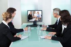 Zakenlui die op een online presentatie letten Stock Foto's