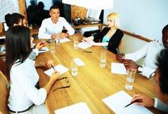 Zakenlui die vergadering hebben rond lijst Stock Fotografie
