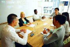 Zakenlui die vergadering hebben rond lijst Stock Afbeelding