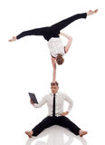 Zakenman-acrobaten die met laptop in studio stellen Stock Foto