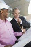 Zakenman And Architect Looking bij Blauwdruk Stock Afbeeldingen