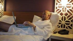 Zakenman in Badjas die op het bed in het hotel liggen en laptop met behulp van stock footage