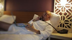 Zakenman in Badjas die op het bed in het hotel liggen en laptop met behulp van stock video