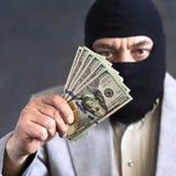 Zakenman in balaclava met dololors in handen op donkere achtergrond misdaad diefstal royalty-vrije stock afbeeldingen