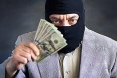 Zakenman in balaclava met dololors in handen op donkere achtergrond misdaad diefstal royalty-vrije stock foto's