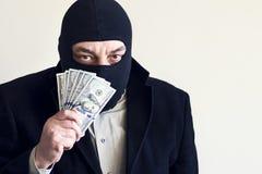 Zakenman in balaclava met dololors in handen op donkere achtergrond misdaad diefstal royalty-vrije stock foto
