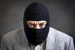 Zakenman in balaclava op een donkere achtergrond misdaad diefstal royalty-vrije stock afbeeldingen