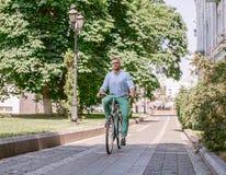 Zakenman berijdende fiets om aan stedelijke straat in ochtend te werken stock fotografie