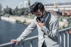 zakenman in beschermend masker die probleem met ademhaling op brug en het leunen op traliewerklucht hebben stock fotografie