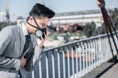 zakenman in beschermend masker die probleem met ademhaling op bruglucht hebben royalty-vrije stock afbeelding
