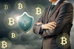 Zakenman beschermend schild en bitcoin Stock Fotografie