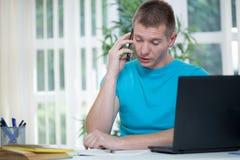 Zakenman bij bureau bezig het spreken op telefoon en het bekijken bij Stock Foto's
