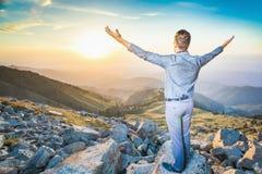 Zakenman bij de bovenkant van de berg zitting en het denken Stock Foto