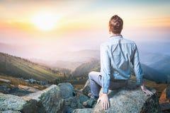 Zakenman bij de bovenkant van de berg zitting en het denken Stock Afbeeldingen