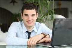 Zakenman bij lijst met laptop in bureau. Stock Foto
