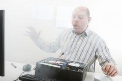 Zakenman Blowing Smoke Emerging van Computerchassis royalty-vrije stock afbeeldingen
