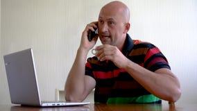 Zakenman in bureau die smartphone en laptop met behulp van Mens die op Telefoon spreken terwijl het Werken aan Laptop in Koffie stock footage