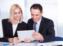 Zakenman And Businesswoman Looking bij Digitale Tablet royalty-vrije stock fotografie