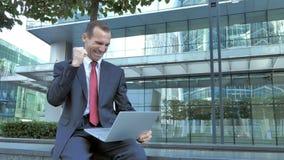 Zakenman Celebrating Results op Laptop Zitting buiten Bureau stock videobeelden