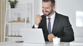 Zakenman Celebrating Success, die aan Laptop werken stock footage