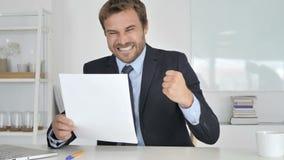 Zakenman Celebrating Success terwijl het Lezen van Documenten stock footage