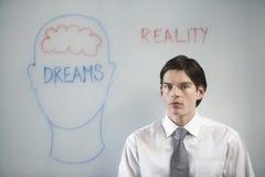 Zakenman Confused Between Dream en Werkelijkheid stock foto