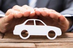 Zakenman Covering Paper Car op Lijst royalty-vrije stock afbeeldingen