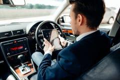 Zakenman in de auto met de tablet Royalty-vrije Stock Afbeelding