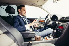 Zakenman in de auto met de tablet Stock Afbeelding