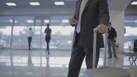 Zakenman in de luchthaven met zijn telefoon en koffer stock video