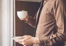 Zakenman de status dichtbij venster en het houden van koffiekop ontspannen terwijl het werken stock foto
