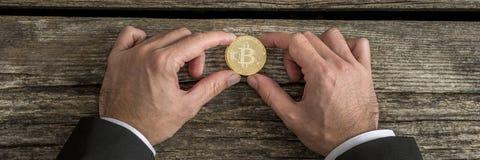Zakenman die één gouden Bitcoin in een breed bebouwd beeld houden stock foto