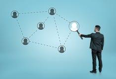 Zakenman die één van de sociale die netwerkpictogrammen vergroten door gestippelde lijnen aan meer magnifier worden verbonden Stock Afbeelding